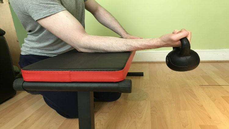 A man performing kettlebell wrist curls