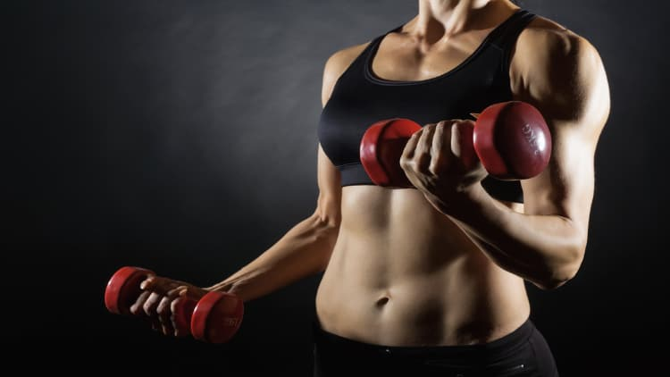 Lean woman lifting red dumbbells