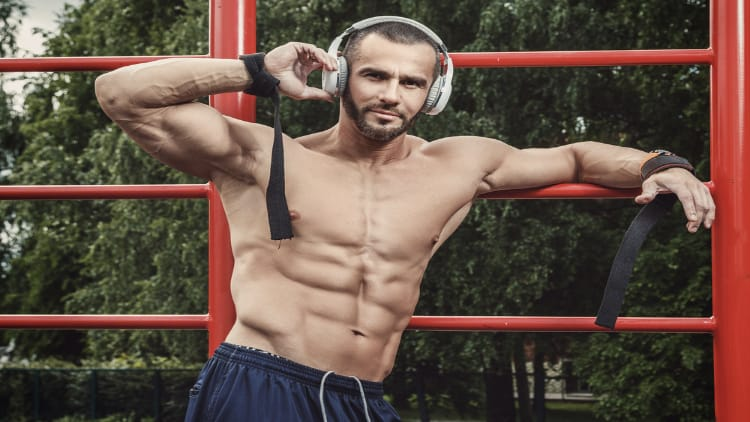Muscular man wearing headphones while working out at the park