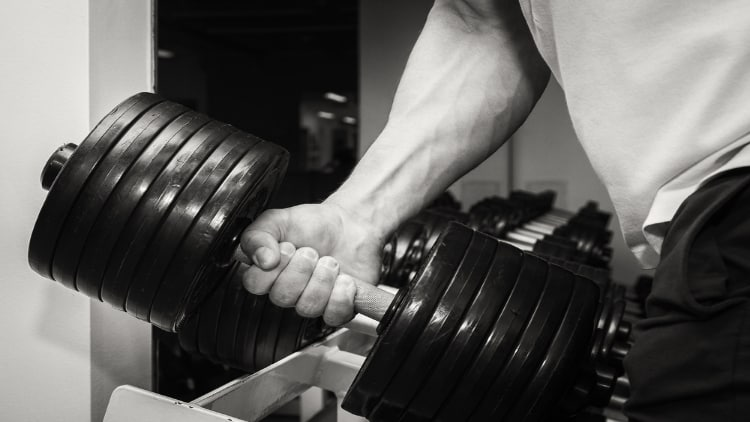 Close up of a man lifting a huge dumbbell