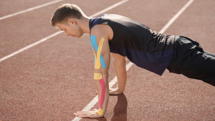 Man doing push up training with physio tape on his arm