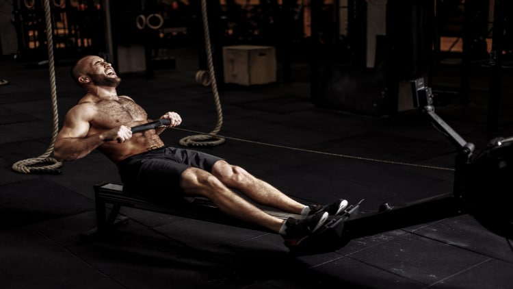 Man using a rowing machine indoors