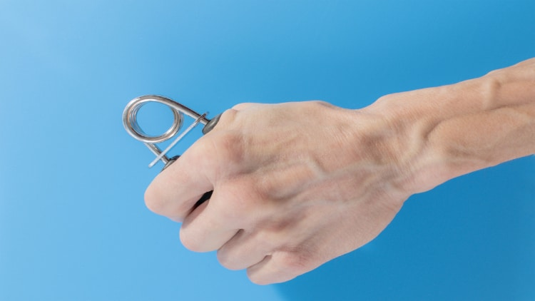 Close up of a man squeezing a hand strengthener