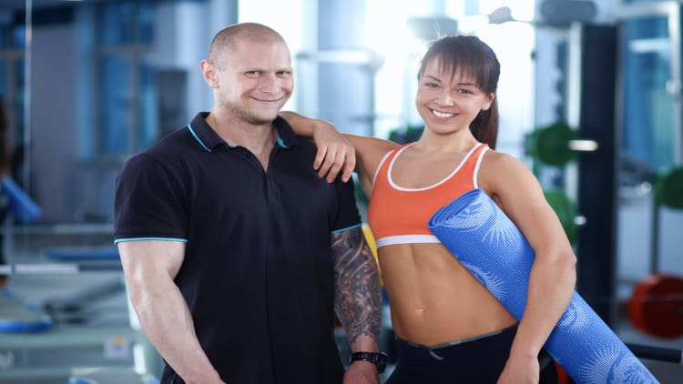 A man and a woman standing together in the gym