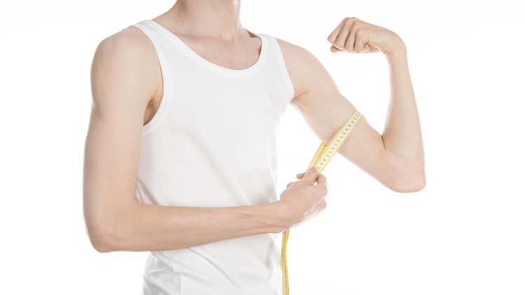 Skinny guy measuring his arm size