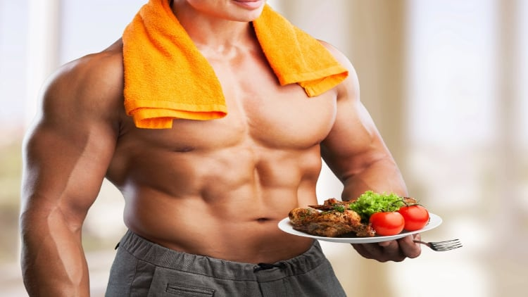 Muscular man holding a plate of food