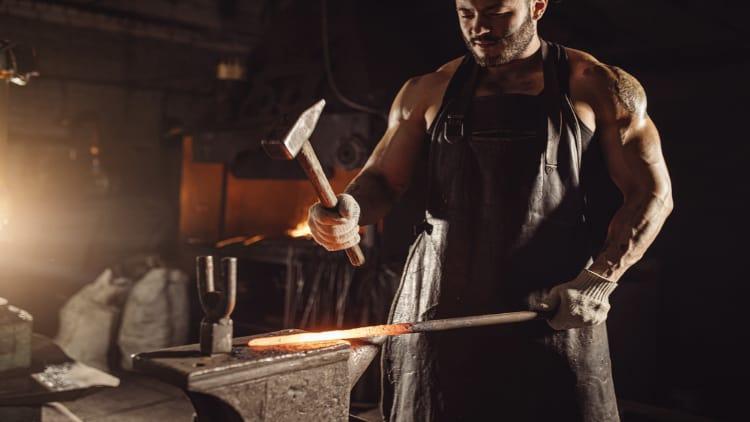Muscular blacksmith holding a hammer