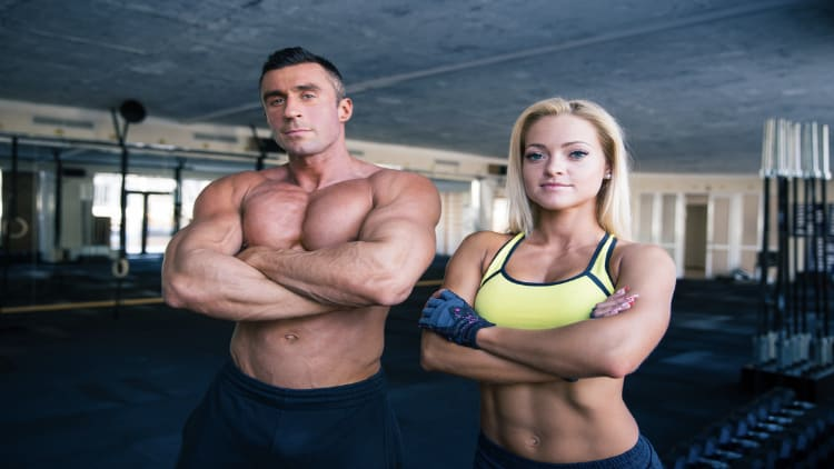 Muscular couple folding their arms