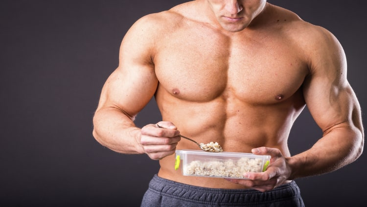 Muscular man eating healthy food from a plastic container