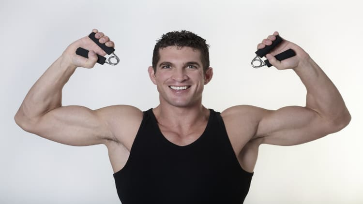 Muscular man squeezing two hand grip trainers