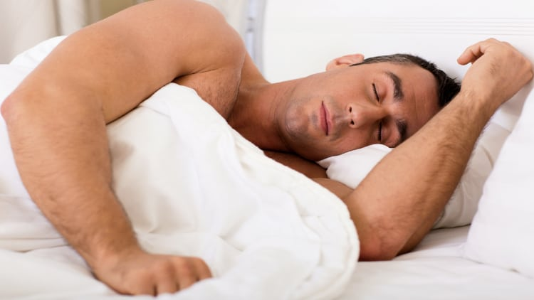 A muscular man sleeping in bed