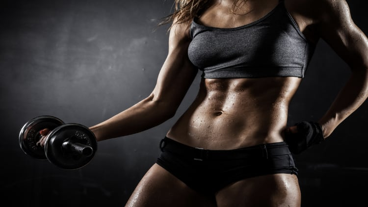 A muscular woman holding a dumbbell