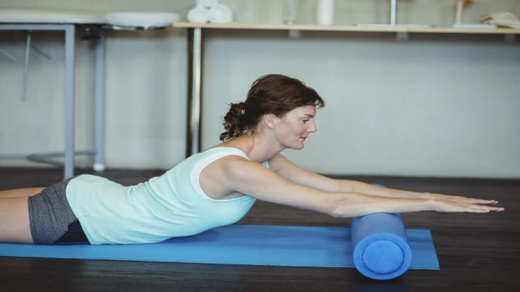 Woman performing myofascial release for her forearms