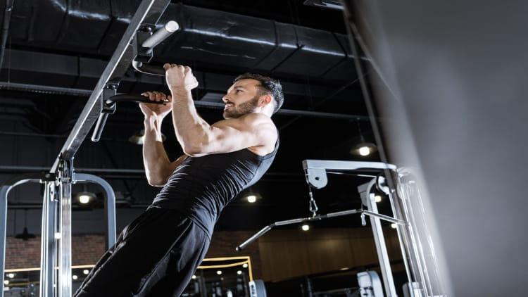 Man performing neutral grip chin ups in the gym