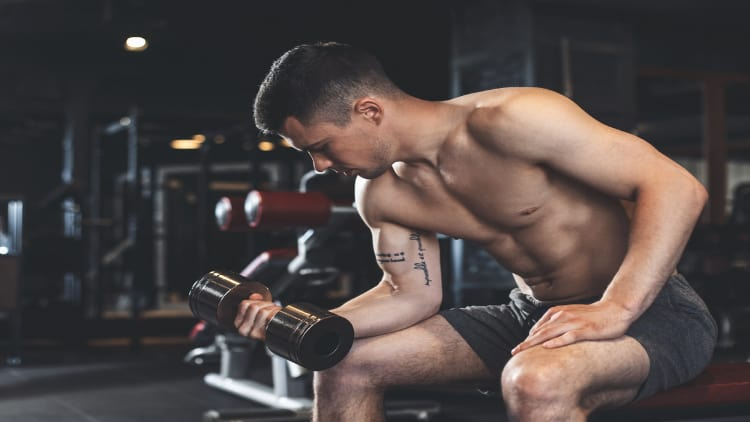 Man performing a one arm dumbbell wrist curl