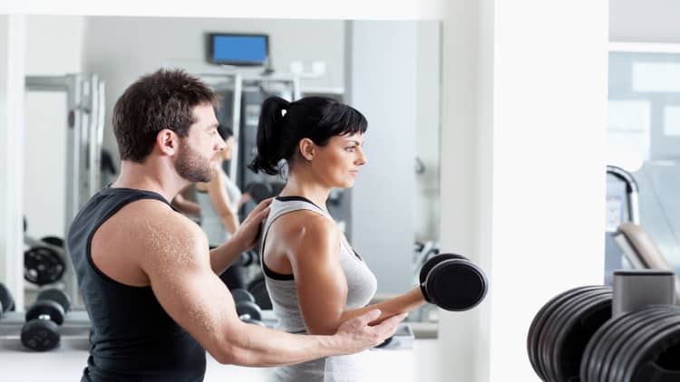 Personal trainer coaching his client during dumbbell curls