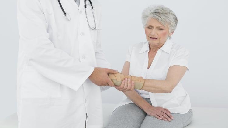 Physiotherapist examining a senior woman's wrist