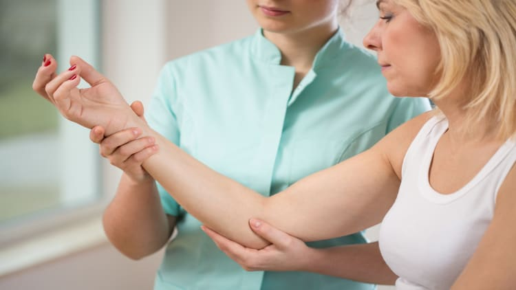 Physiotherapist flexing a patient's elbow