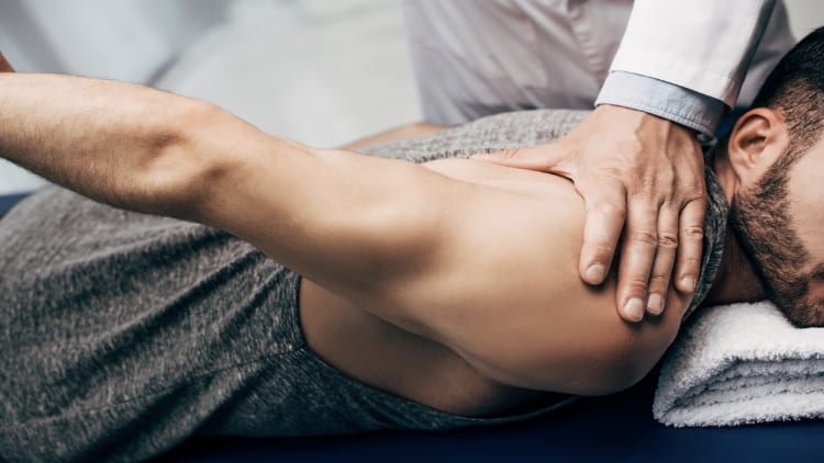 A physiotherapist stretching his patient's arm while the patient lays on his stomach