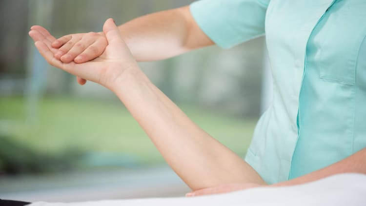 Physiotherapist touching a woman's hand