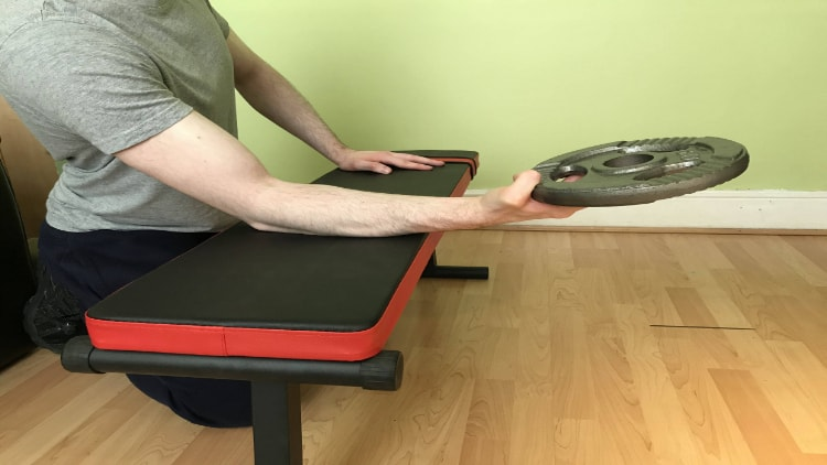 A man performing a plate forearm curl over a bench