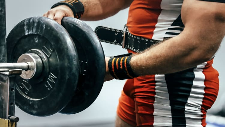 A powerlifter loading weight discs onto a barbell