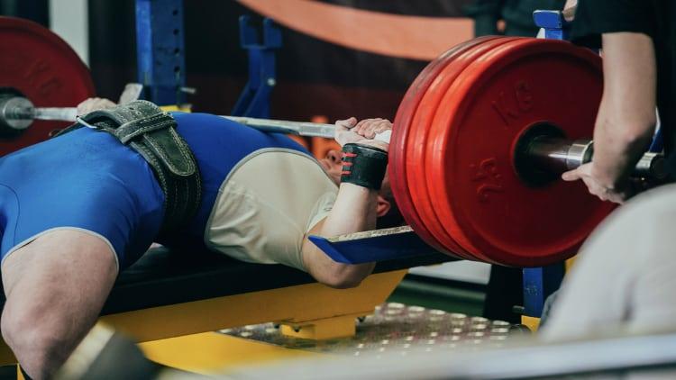 Man bench pressing at a powerlifting meet