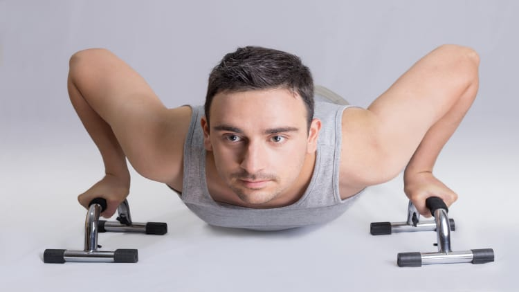 Man performing push ups on handles