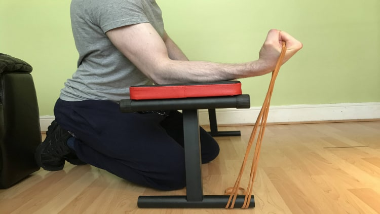 A man performing resistance band forearm curls