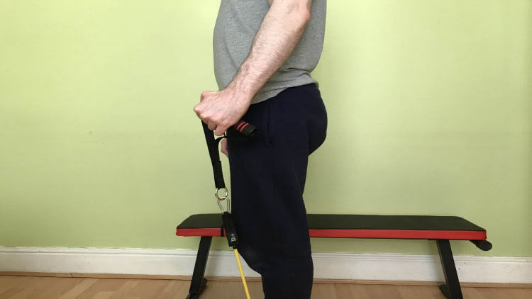 A man doing a resistance band radial deviation