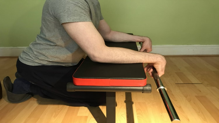 Man overextending his wrists during reverse barbell wrist curls