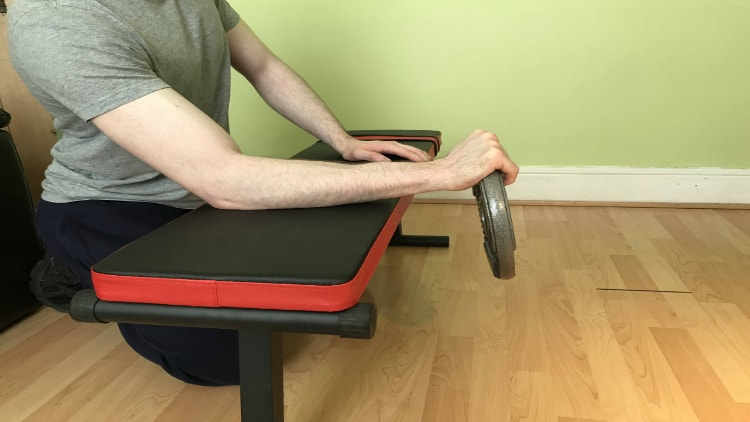 Man performing a reverse plate forearm curl over a bench