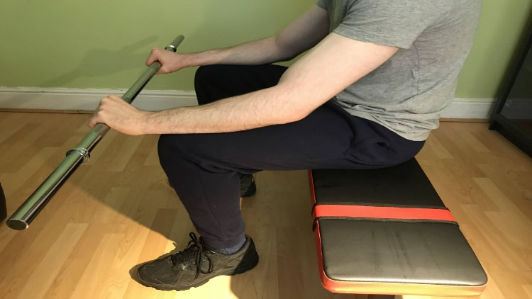 Man performing a reverse wrist curl with a barbell