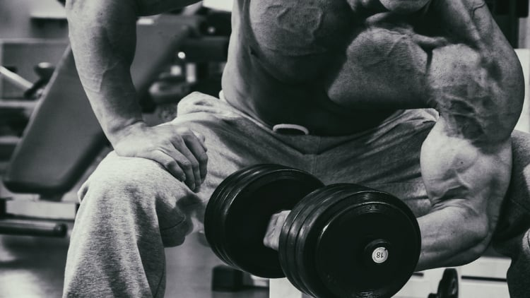Ripped man doing a dumbbell curl