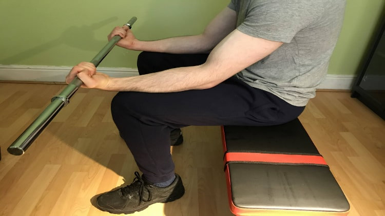 The end position of a seated barbell forearm curl