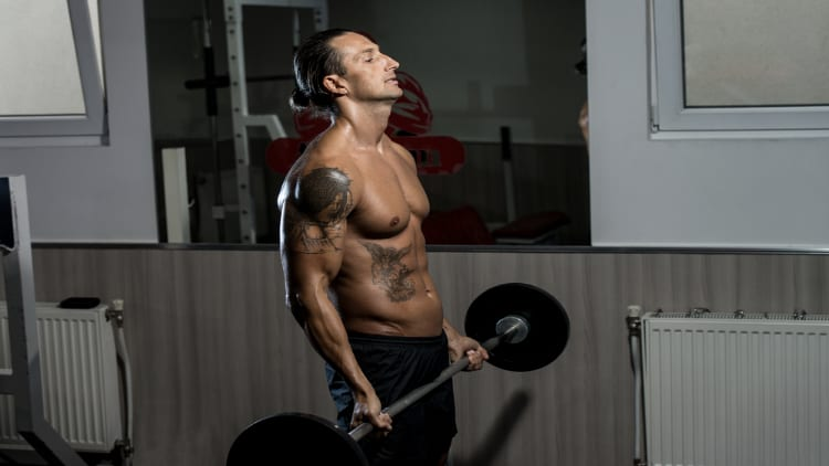 Shirtless man doing a barbell curl