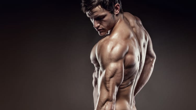 Fitness model flexing his triceps