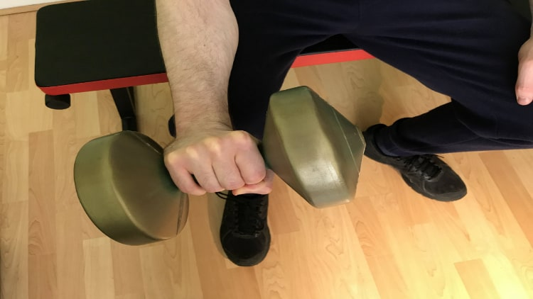 A man performing single arm dumbbell reverse wrist curls