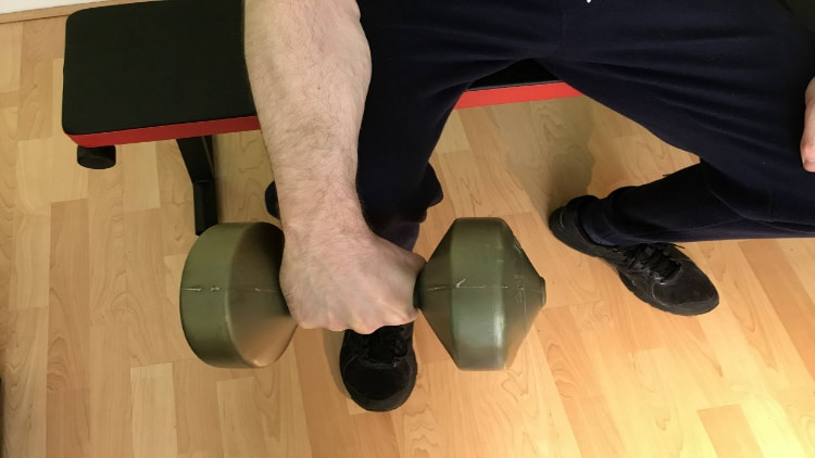 A man doing reverse single arm wrist curls over his knee