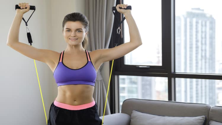 Smiling woman lifting resistance bands at home
