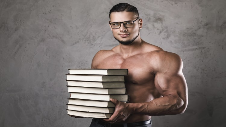 A muscular man wearing glasses and holding books