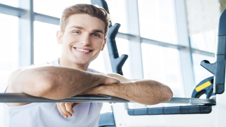 A smiling man resting his arms on a barbell at the gym