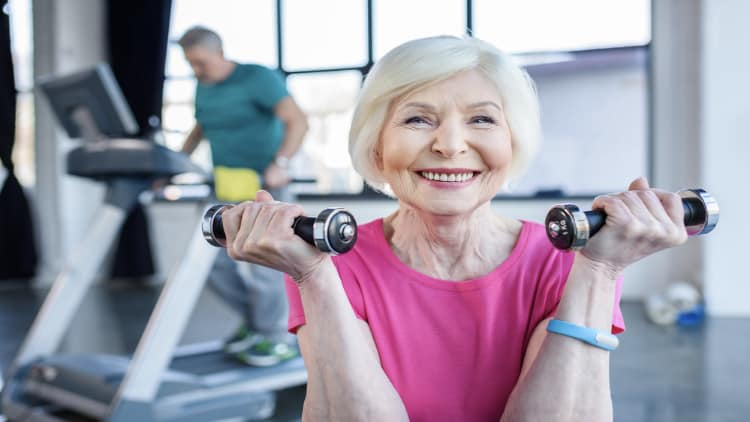 A smiling senior woman holding two dumbbells