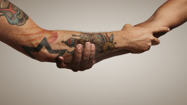 Two men performing the Spartan handshake from Roman times, clasping one another's forearms