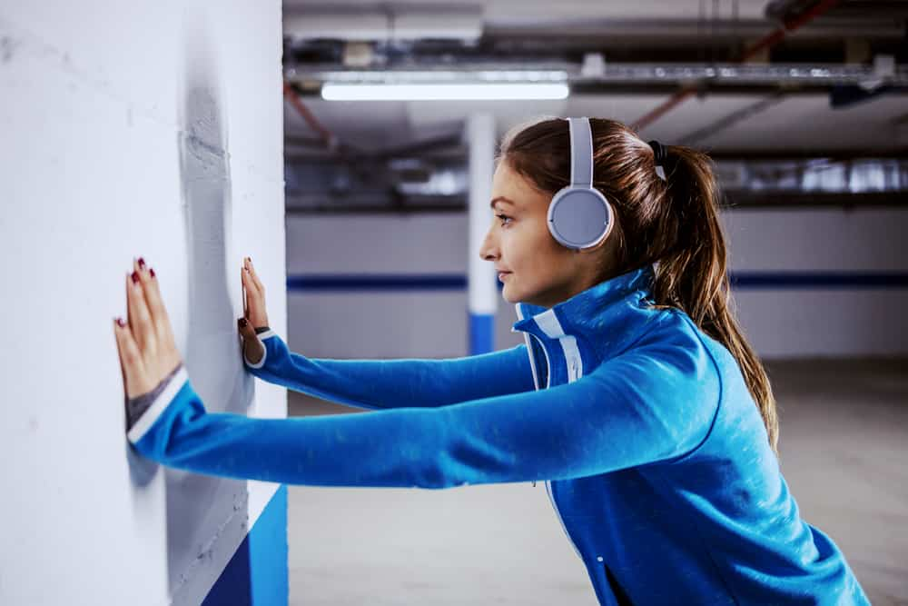A sporty woman pushing against a wall