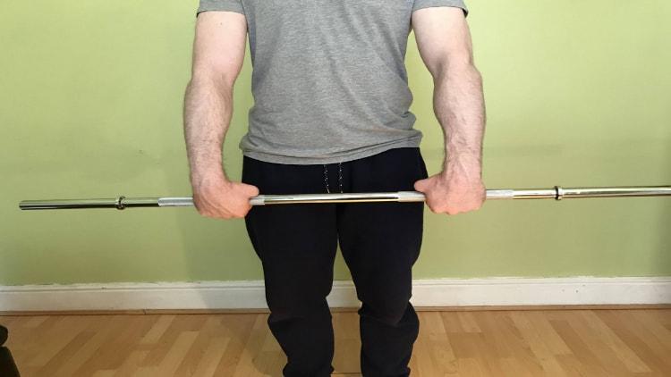 A man doing a standing barbell wrist curl
