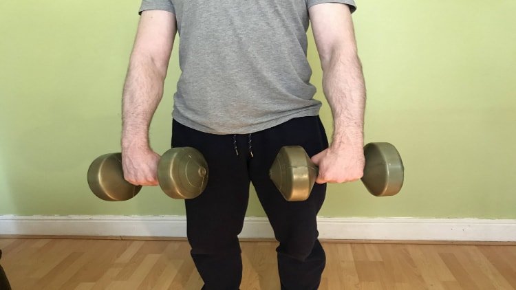 Man performing standing wrist curls with dumbbells
