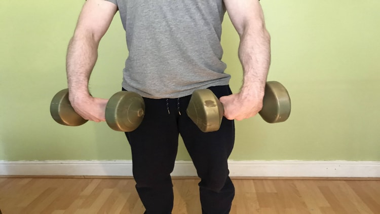 Man performing standing forearm curls with dumbbells