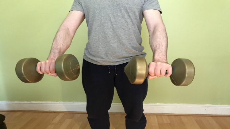 Man doing standing reverse wrist curls with dumbbells
