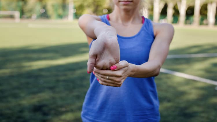 Sporty woman stretching her forearm flexors outside